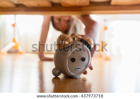 Closeup photo of beautiful girl reaching for alarm clock under the bed - stock photo