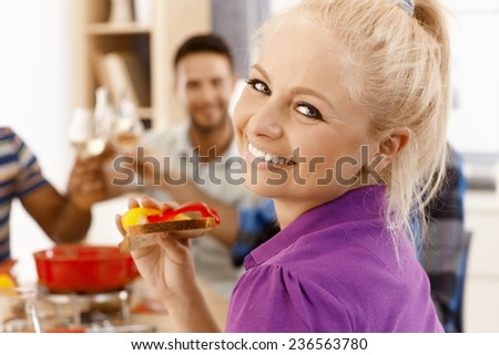 Closeup photo of beautiful young woman dining with friends, smiling happy, looking at camera. - stock photo