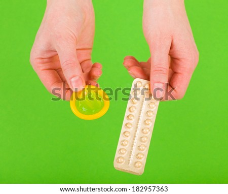 Closeup photo of birth control pills and condom holding in hands