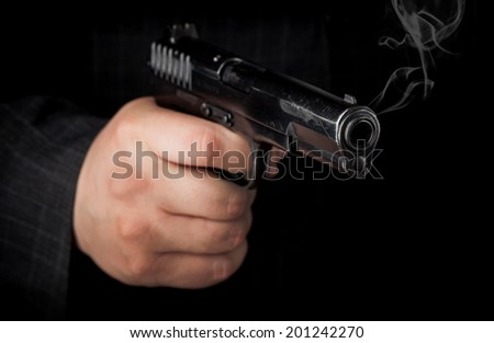 Closeup photo of black pistol in hand with smoke - stock photo