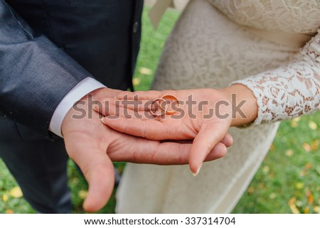 Closeup photo of bride and groom holding golden wedding rings on hands - stock photo