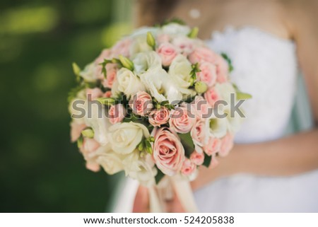 closeup photo of bride holding a flower bouquet. wedding decoration background