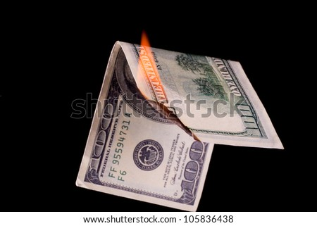 Closeup photo of burning dollar banknote on black background - stock photo
