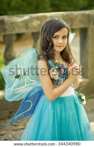 Closeup photo of caucasian beautiful little girl with curly loose dark hair in blue fluffy dress with flowers and wings keep hands folded in day outdoor, vertical picture