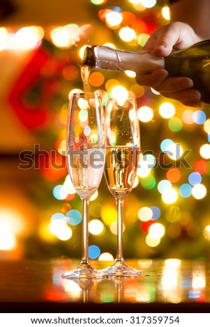 Closeup photo of champagne being poured in glasses against Christmas lights - stock photo