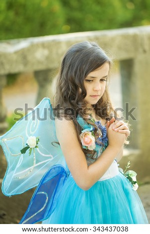 Closeup photo of charming white little girl with curly loose dark hair dressed as fairies with wings keep hands folded in day outdoor, vertical picture - stock photo
