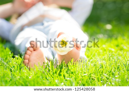 Closeup photo of children`s feet with flower in spring park - stock photo