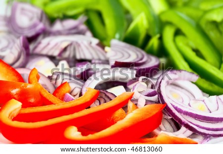 Closeup photo of chopped red and green peppers surrounding a chopped red onion. Short depth of field, with focus on the red pepper.