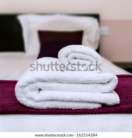 Closeup photo of clean towels and soap in a hotel room - stock photo