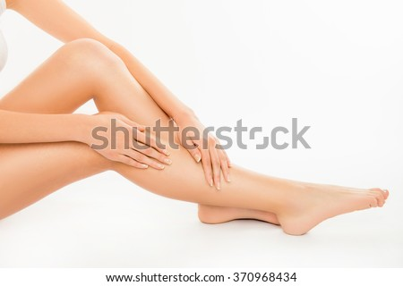Closeup photo of cute pretty young woman touching her legs - stock photo