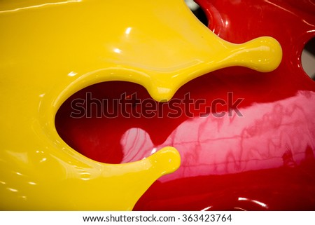 Closeup photo of 3D flowing yellow and red paint - stock photo