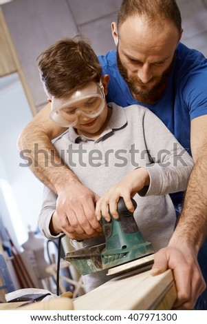 Closeup photo of diy father teaching son tinkering, using jig saw. - stock photo