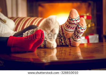 Closeup photo of family warming feet at fireplace - stock photo