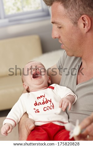 Closeup photo of father holding crying baby. My daddy is cool is written on baby's top. - stock photo