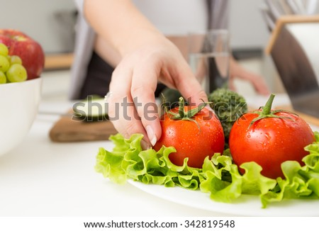 Closeup photo of female hand taking fresh tomato from plate