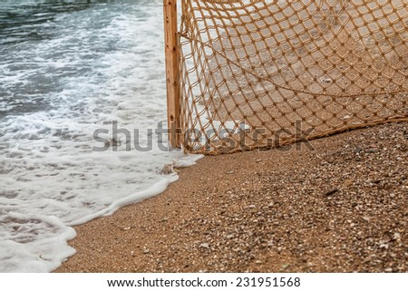Closeup photo of fishing net on sandy beach at sea waves - stock photo