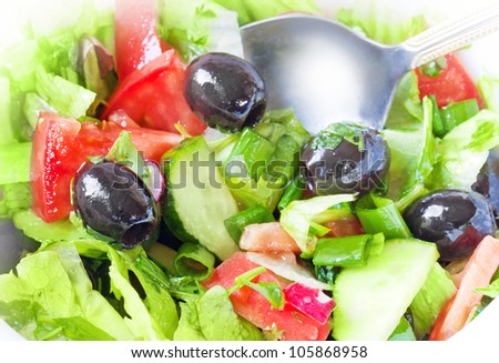 Closeup photo of fresh side dish with green salad, tomatoes, olives, cucumbers and a metal spoon