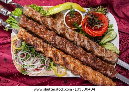 Closeup photo of fried beef kebabs on a skewer with vegetables