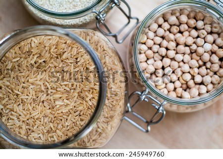 closeup photo of glass jars with brown rice, chickpeas, and quinoa - stock photo