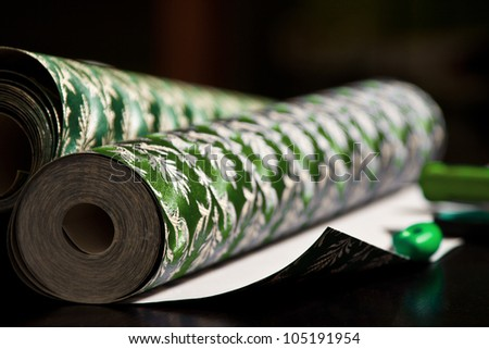 Closeup photo of green wallpaper rolls laying on table with selective focus - stock photo