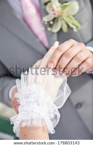 Closeup photo of groom putting wedding