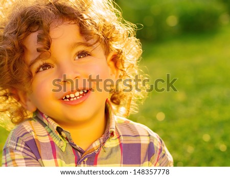 Closeup photo of happy little boy having fun on fresh green grass in the park, adorable kid enjoying sunny day, happy summer holidays - stock photo