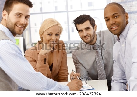 Closeup photo of happy young businessteam working together, smiling, looking at camera. - stock photo
