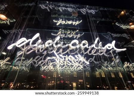 "Closeup photo of illuminated word ""Dedicated"" on street of Salzburg at night - stock photo"