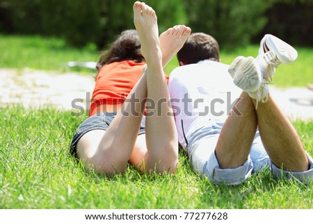 Closeup photo of legs of lying couple lying on the grass - stock photo