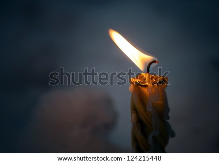 Closeup photo of little candle flame in the dark - stock photo
