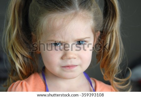 Closeup photo of little girl shows her furrowed brow and irritated frown. - stock photo