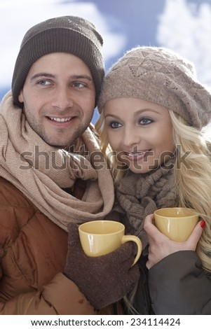 Closeup photo of loving couple drinking tea at wintertime outdoors, looking away. - stock photo