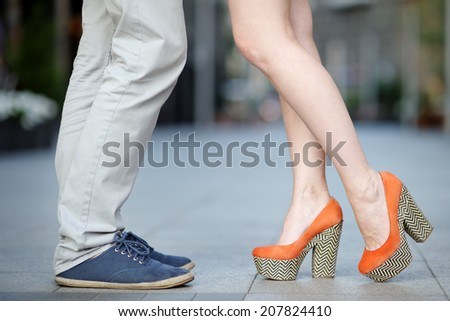 Closeup photo of male and female legs during a date  - stock photo