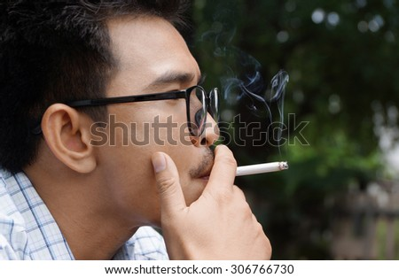 Closeup photo of man hold a smoking in outdoor and wearing a spectacles.