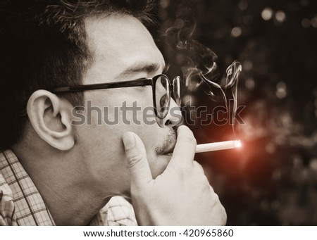 Closeup photo of man hold a smoking in outdoor and wearing a spectacles sepia color tones.
