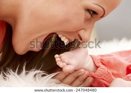 Closeup photo of mother holding and biting tiny bare baby foot. Side view. - stock photo