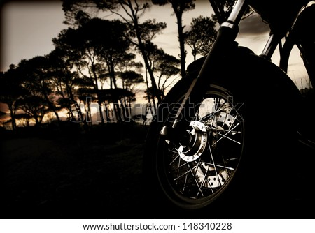 Closeup photo of motorcycle wheel on sunset, active lifestyle, extreme sport, dangerous transport in the forest at night, journey and freedom concept - stock photo