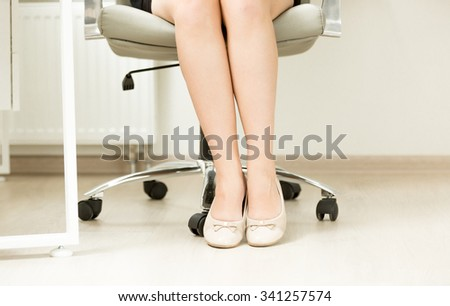 Closeup photo of of businesswomen feet in ballet flats under office table - stock photo