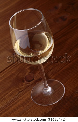 Closeup photo of one full clear glass goblet with white semisweet grape wine standing on brown wooden table top, vertical picture - stock photo