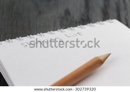 closeup photo of open empty notepad with shopping list phrase, on wood table - stock photo