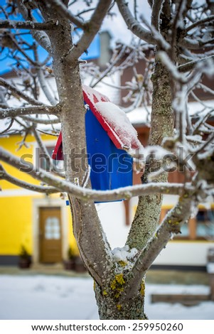 Closeup photo of painted blue bird house hanging on tree at snowy day - stock photo