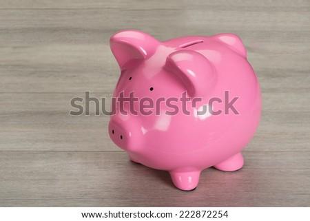Closeup photo of piggybank on wooden table - stock photo