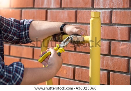 Closeup photo of plumber installing new valve on yellow pipe outside of house - stock photo