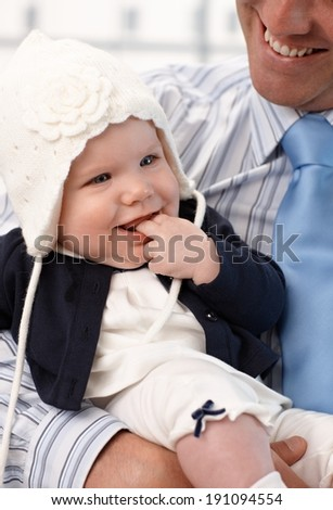 Closeup photo of pretty baby girl in father's arms, smiling. - stock photo
