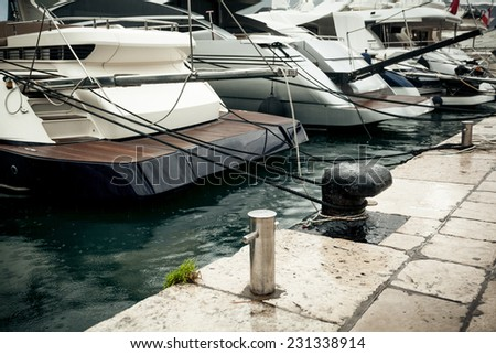 Closeup photo of row of moored yachts at rainy day - stock photo