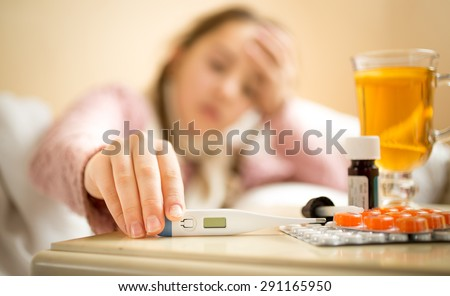 Closeup photo of sick girl taking digital thermometer from bedside table - stock photo