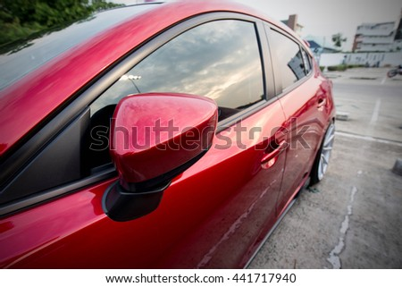 Closeup photo of side rear-view car mirror on a modern red colour car in the evening time - stock photo
