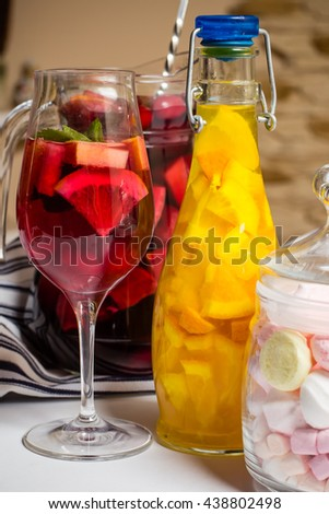 closeup photo of summer bright color fruit painted cocktails, lemonade, wine in glass, metallic bar shaker, studio photo, grey background, party space - stock photo