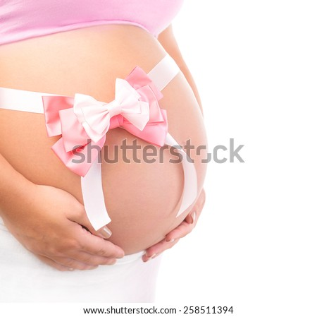 Closeup photo of tummy of pregnant woman with pink ribbon bow isolated on white background, body part, best gift for young family, it's a girl  - stock photo