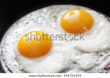 Closeup photo of two scrambled eggs in black frying pan - stock photo